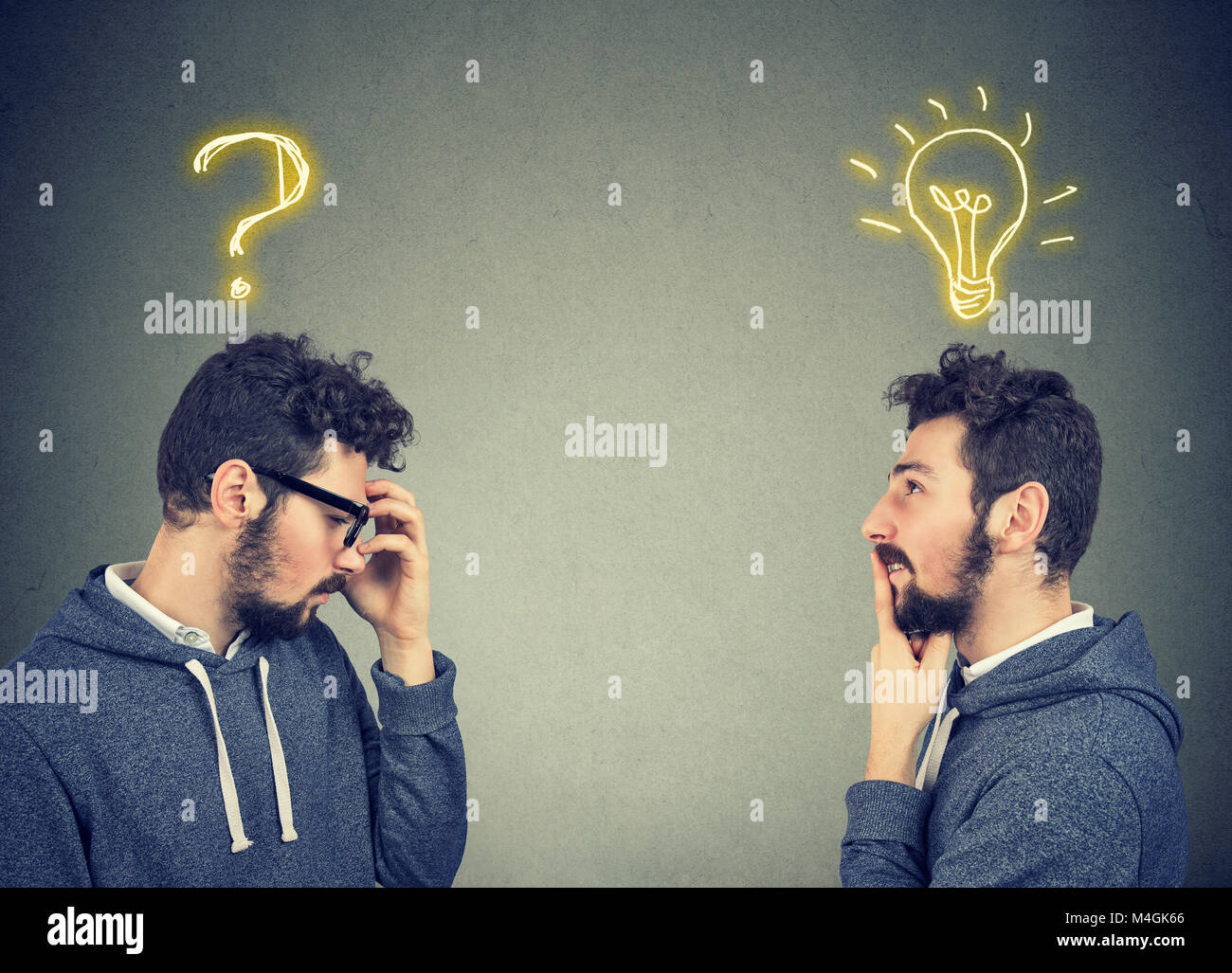 Two men thinking one has a question another solution with light bulb above head isolated on gray background. - Stock Image