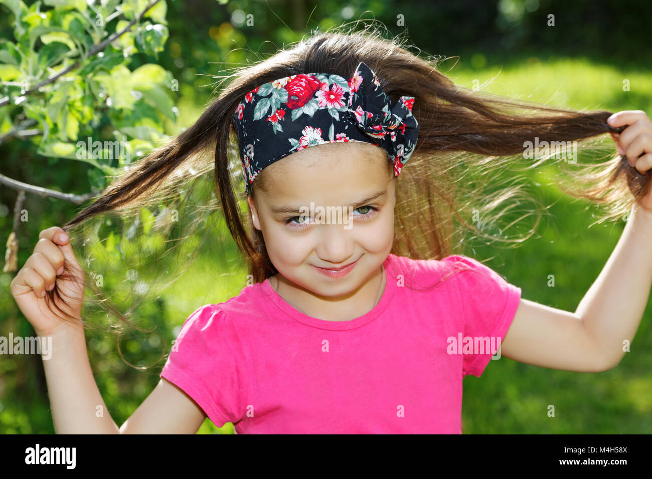 Little girl with bandanas on her head in the park - Stock Image