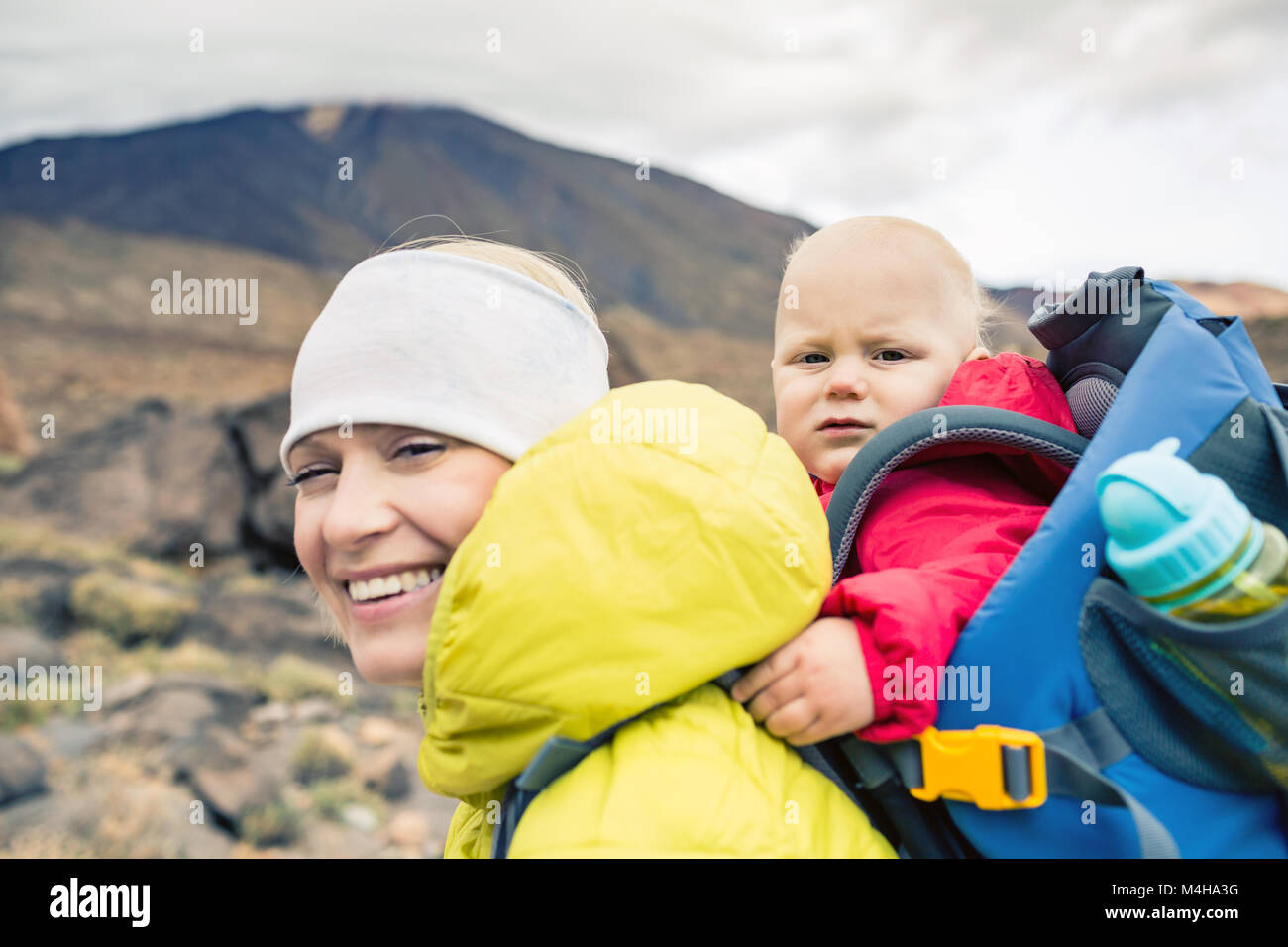 Happy mother with little boy travelling in backpack. Hiking adventure with child on autumn family trip in mountains. - Stock Image