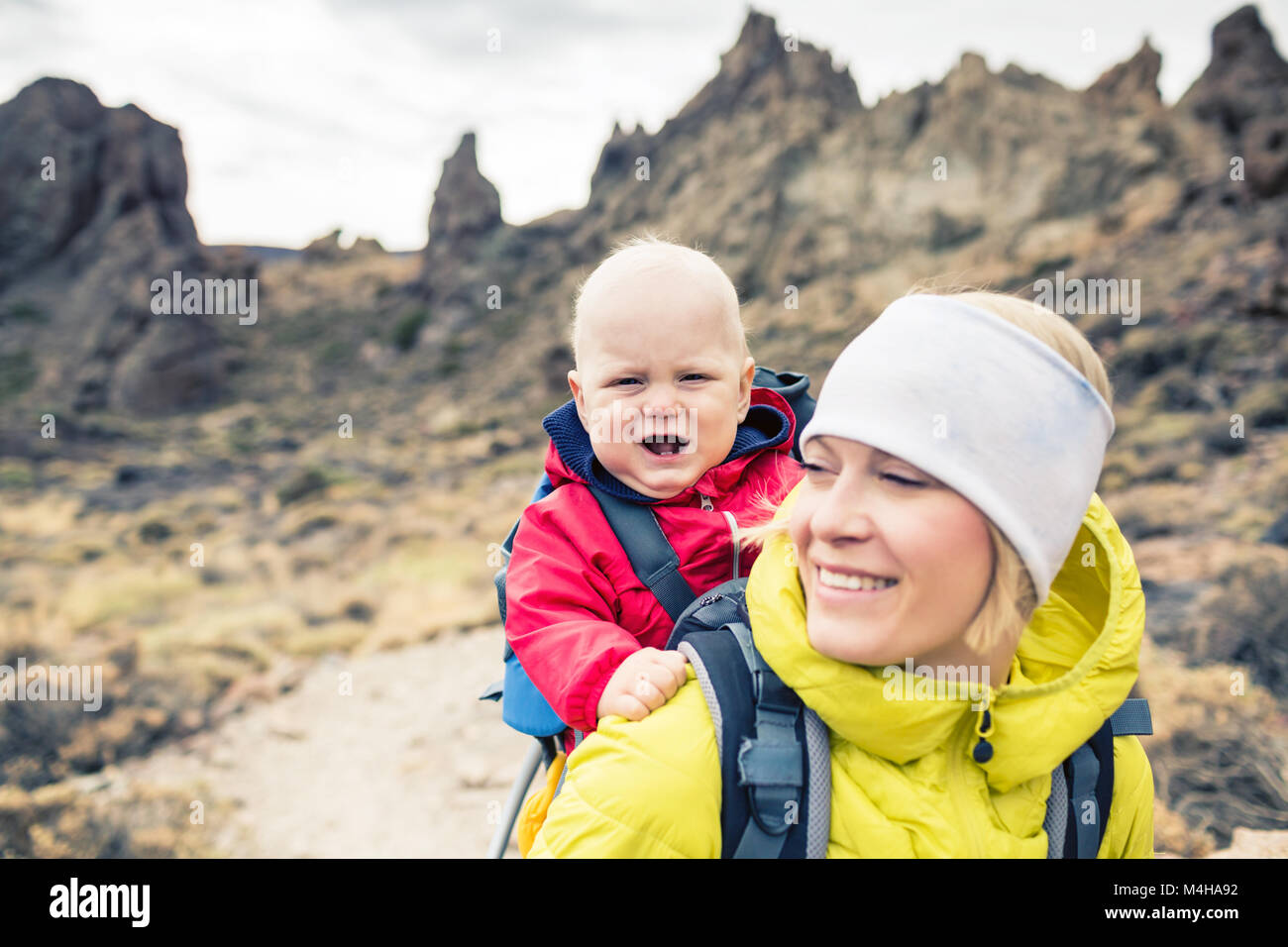 Mother with little boy travelling in backpack. Hiking adventure with child on autumn family trip in mountains. Vacations - Stock Image