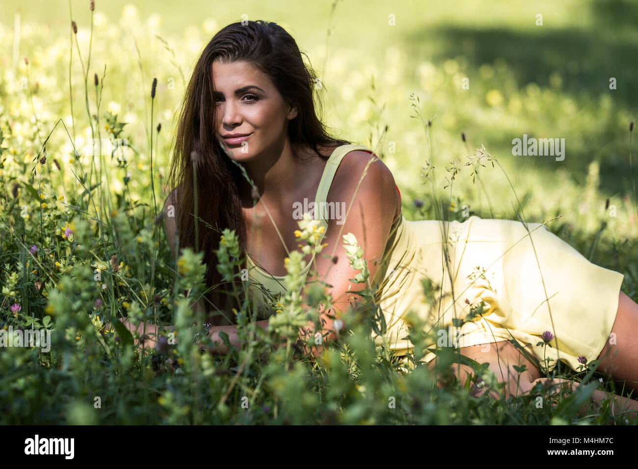 [Image: young-woman-in-summer-dress-is-lying-on-...M4HM7C.jpg]