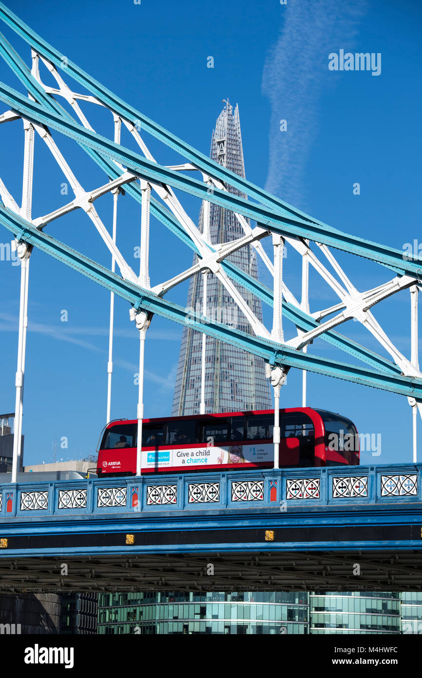 Red London bus crossing Tower Bridge with the Shard in the background, London, England, UK Stock Photo