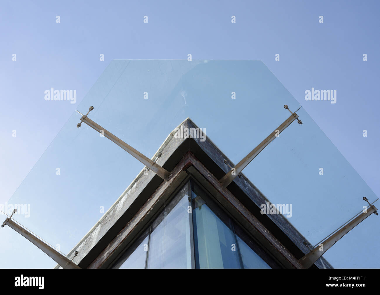 Glass canopy suspended on stainless steel brackets in v Stock Photo