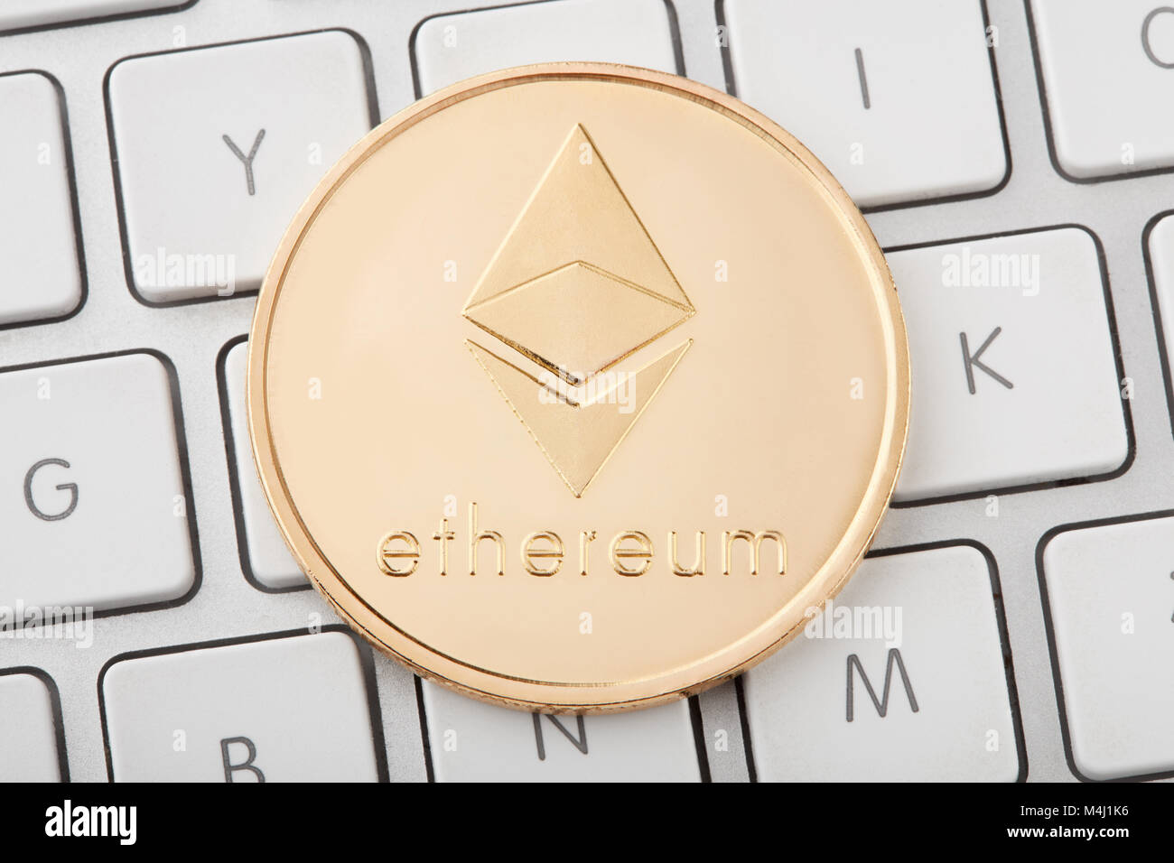 Ethereum golden cryptocurrency coin on keyboard - Stock Image