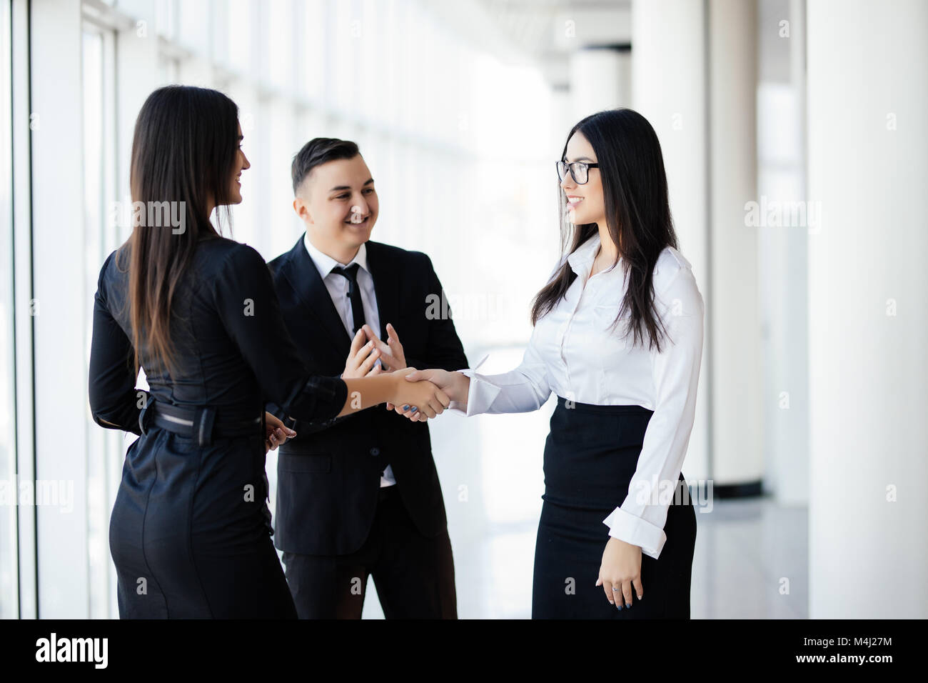 Business partners shaking hands in meeting hall - Stock Image