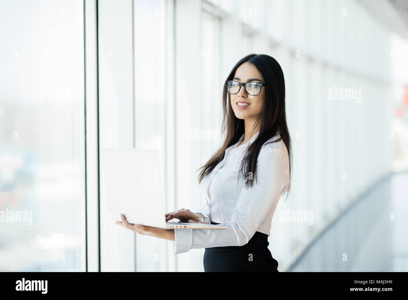 Young business woman working in her luxurious office holding a laptop standing against panoramic window with a view - Stock Image