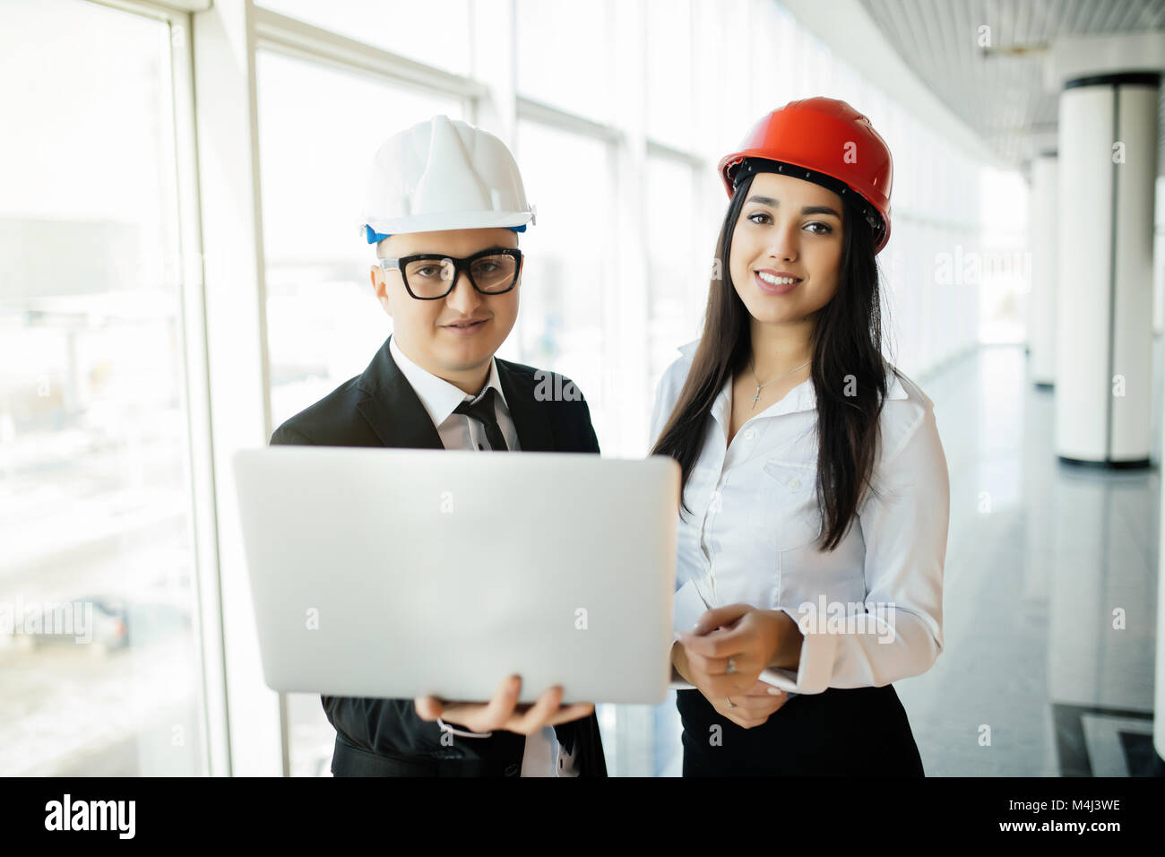 Group of engineer man and woman on construction site for check out the new project with laptop. - Stock Image