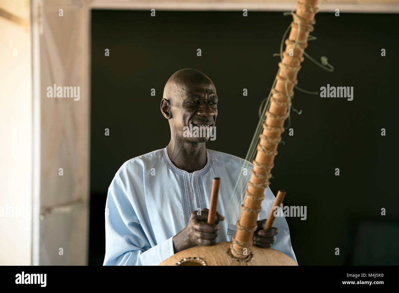An ethnic Mandinka tribesman plays a traditional musical instrument in Jufureh, The Gambia, West Africa. - Stock Image