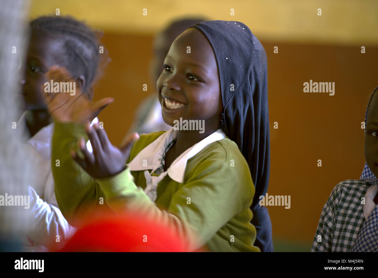 An indigenous Mandinka school girl claps as she sings a song in her village school in The Gambia, West Africa. - Stock Image
