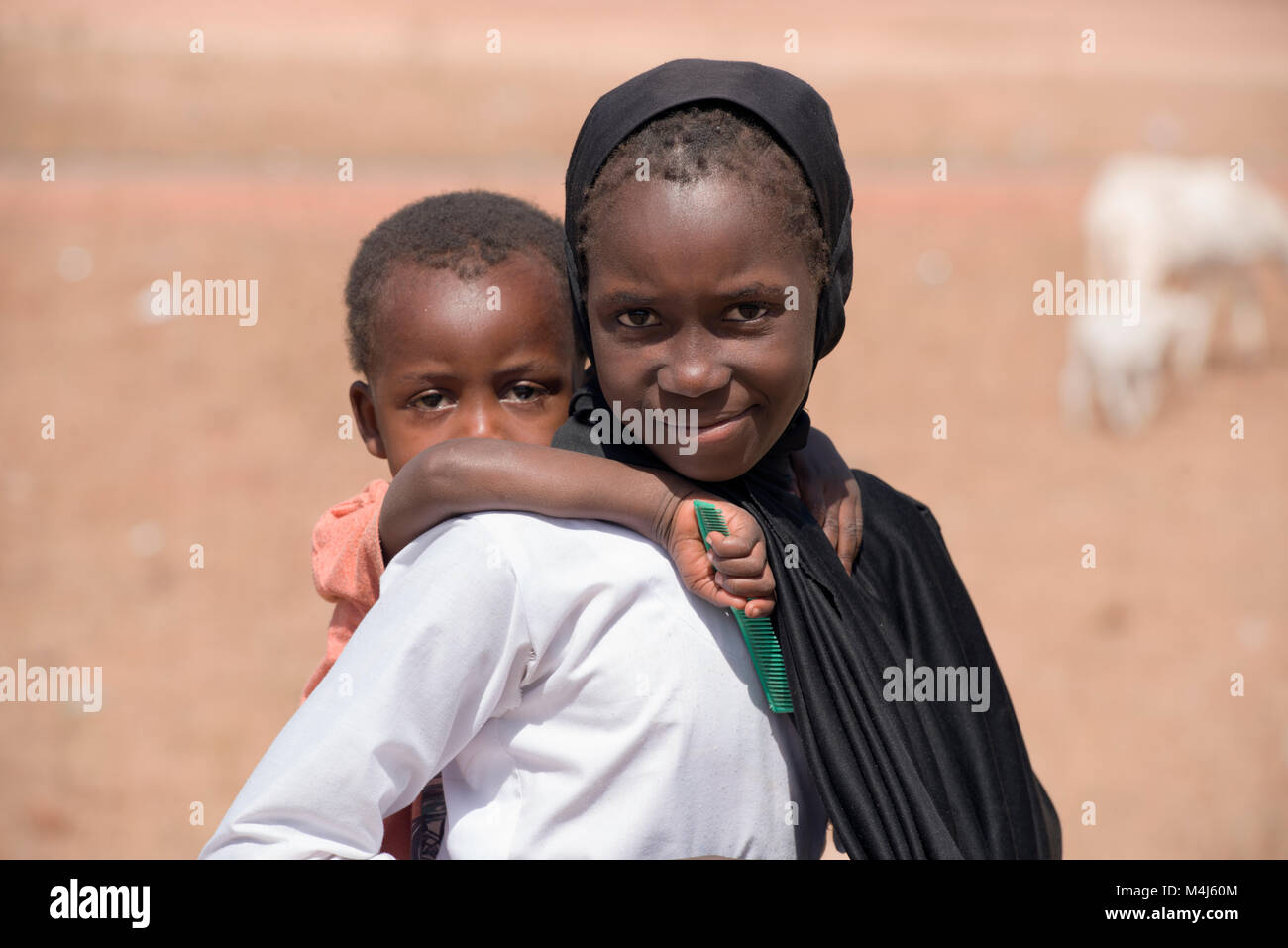 An indigenous Mandingo (Mandinka) girl carrying a young boy in an isolated village in The Gambia, West Africa. - Stock Image