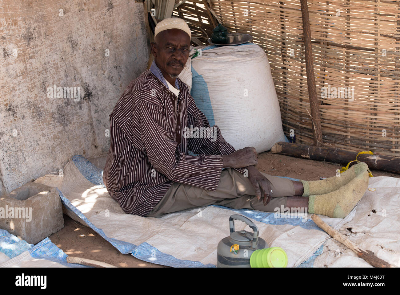 An ethnic Mandinka (Mandingo) man shelters from the midday sun in his basic house in a remote Gambian village, West - Stock Image