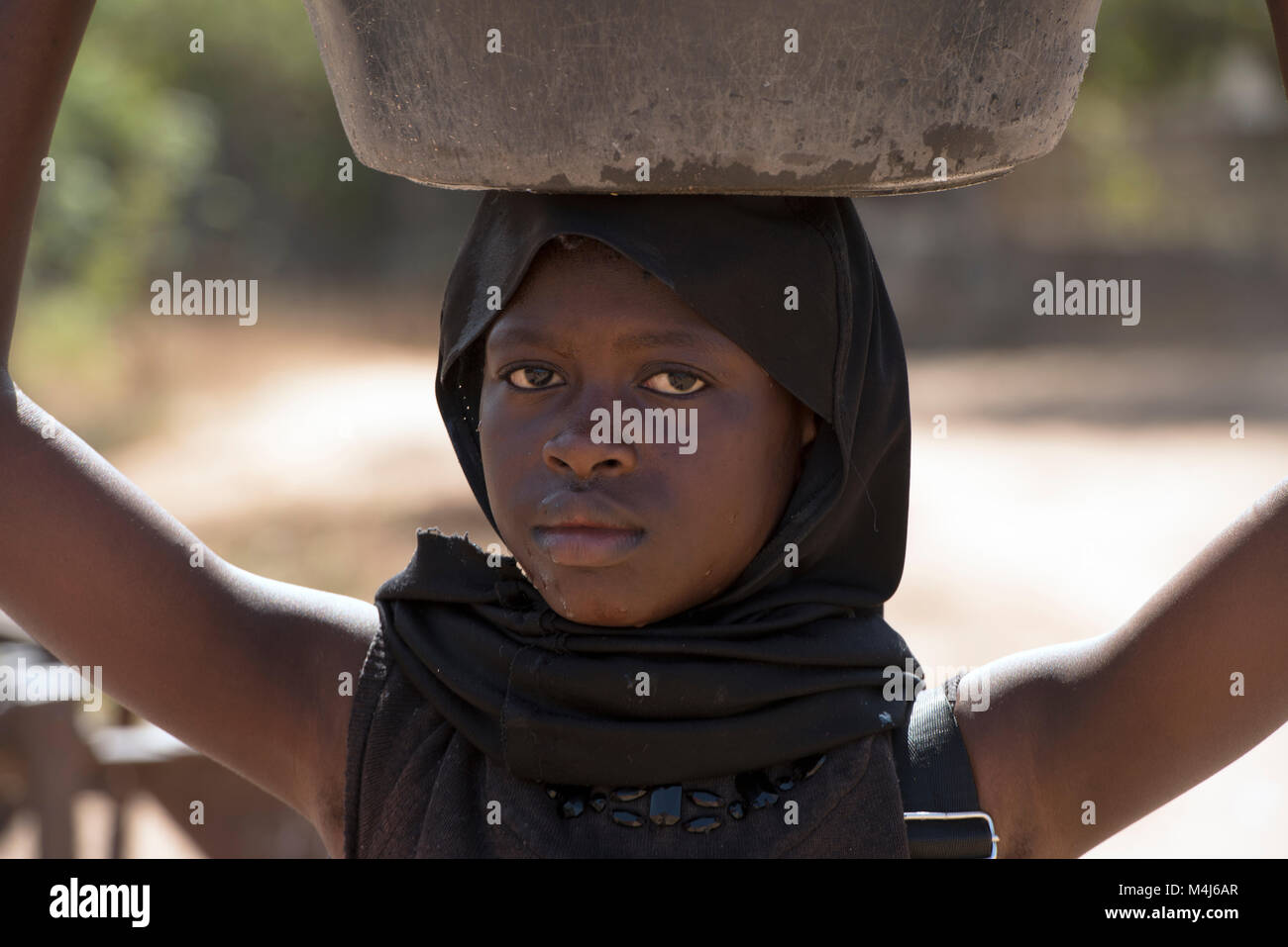 A young Mandinka (Mandingo) girl carrying a pot on her head in her village in The Gambia, West Africa. - Stock Image