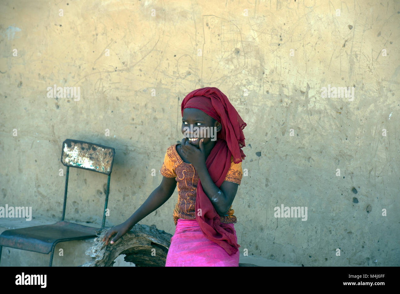 A young, smiling Mandinka girl in colourful clothing in her remote village in The Gambia, West Africa. - Stock Image