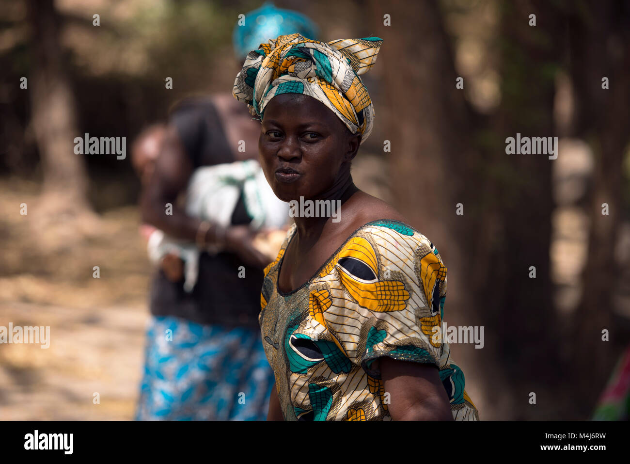 A Mandinka (Mandingo) woman in traditional dress performs traditional dancing in Bintang, The Gambia, West Africa. - Stock Image