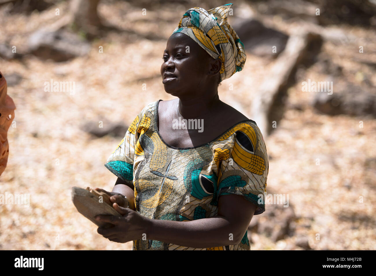 An ethnic Mandingo woman plays a traditional instrument during a ceremonial village dance in The Gambia, West Africa. - Stock Image