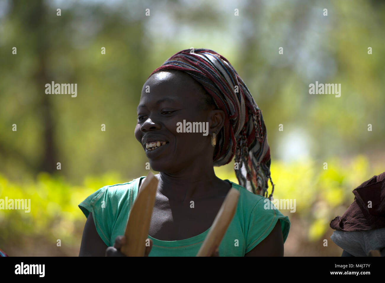 A Mandinka (Mandingo) woman smiles while she dances and plays traditional, ceremonial music in Bintang village, - Stock Image