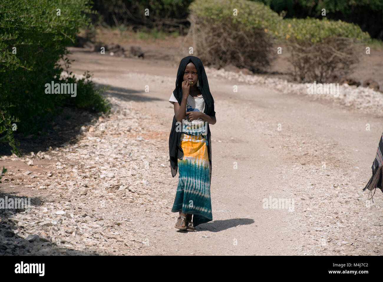 A young Mandingo (Mandinka) tribe girl walking through her village in The Gambia, West Africa. - Stock Image