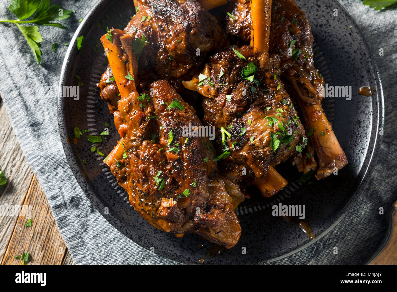 Homemade Braised Lamb Shanks with Sauce and Herbs - Stock Image