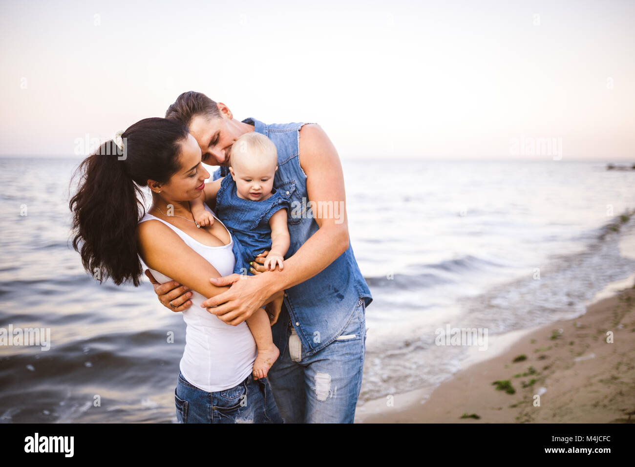 beautiful young family on vacation with baby. The father holds the blonde girl in her arms, and the brunette's - Stock Image