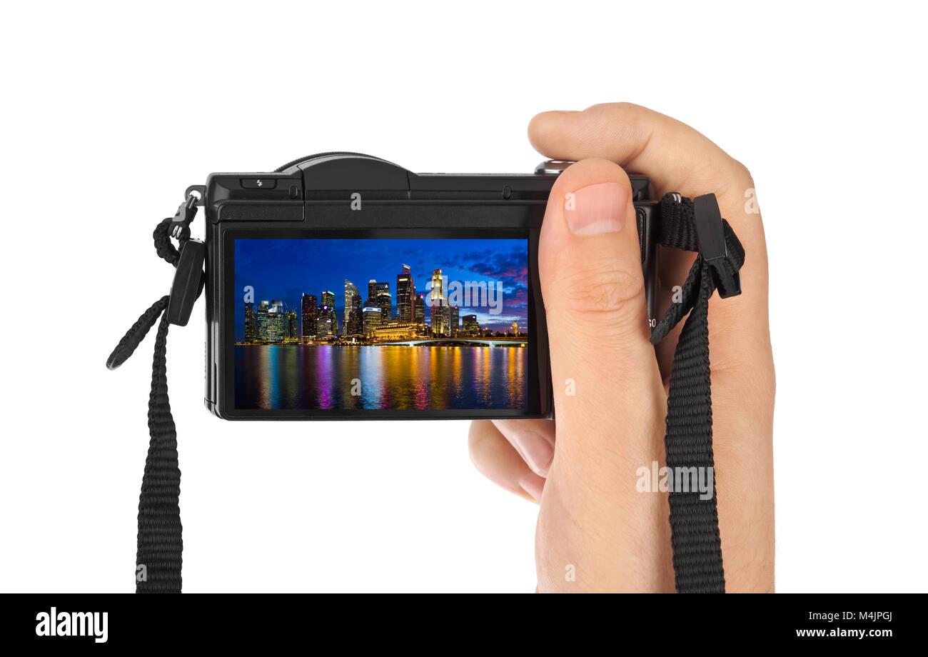 Hand with camera and Singapore city skyline (my photo) - Stock Image
