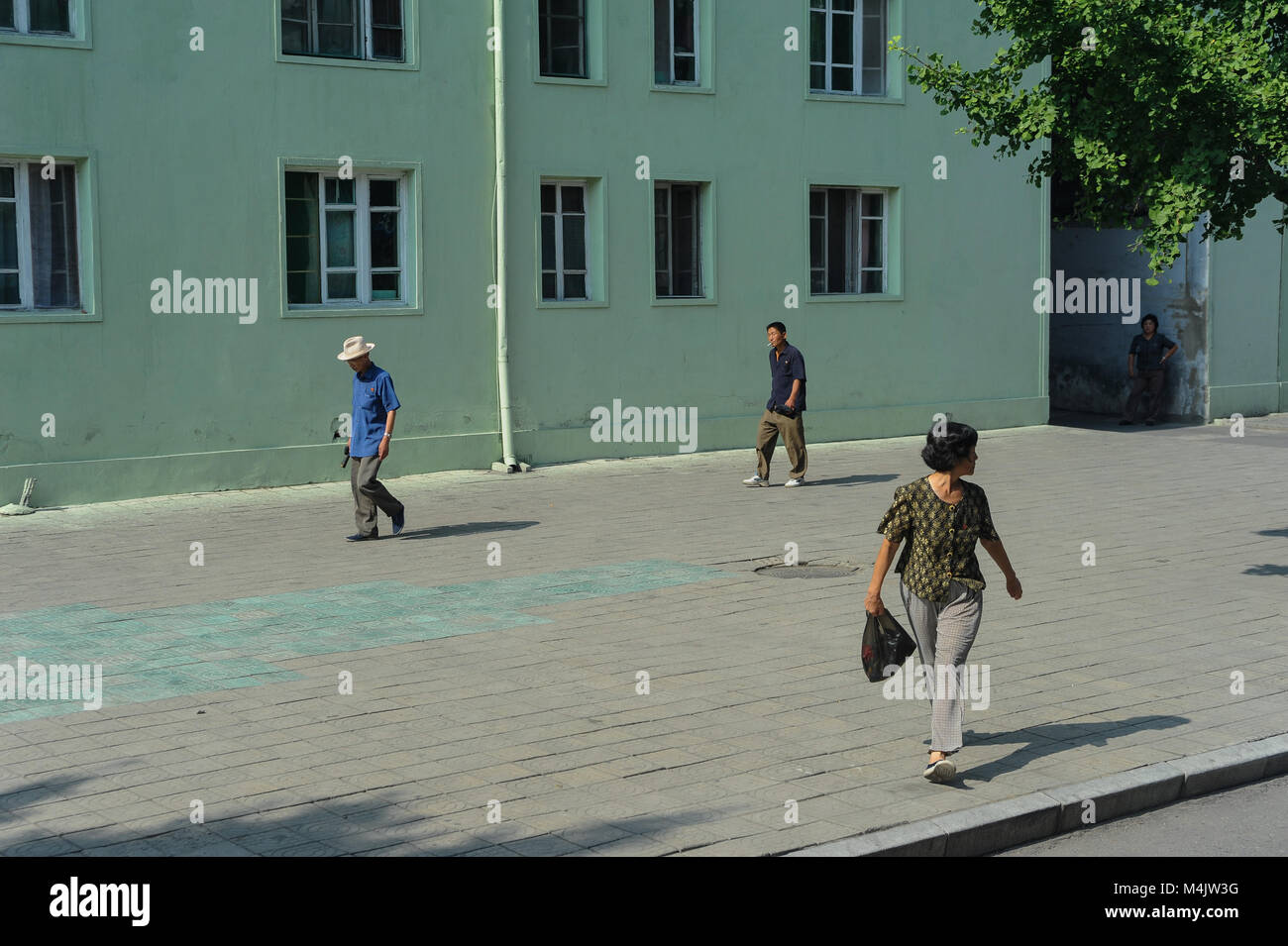08.08.2012, Pyongyang, North Korea, Asia - Pedestrians walk by residential buildings in central Pyongyang. - Stock Image