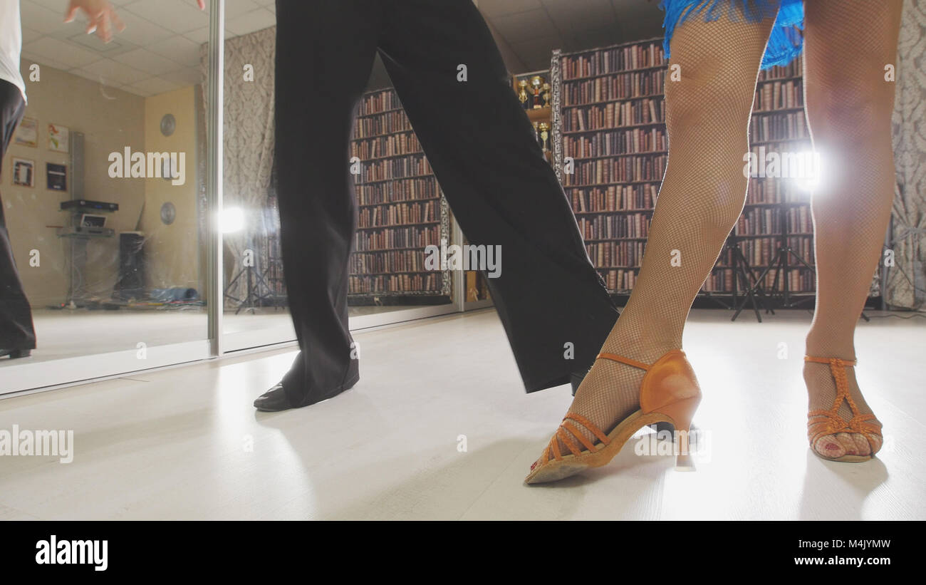 Young beautiful man and woman dancing and rehearsing Latin American dance in costumes in the Studio, focus on feet - Stock Image
