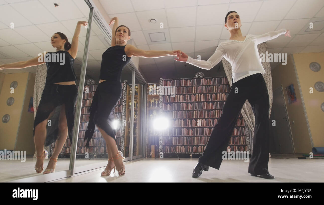 Young attractive man and woman dancing and rehearsing Latin American dance in costumes in the Studio, focus reflection - Stock Image