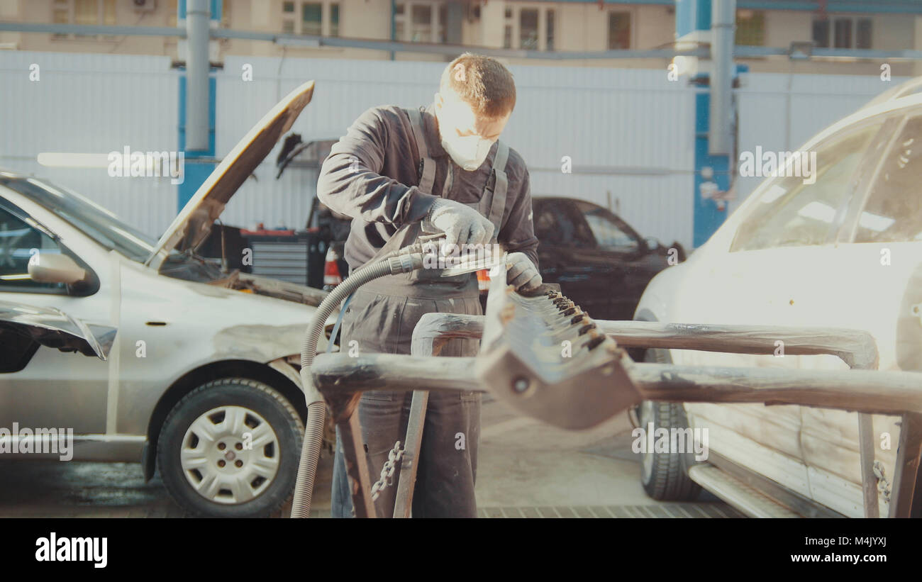 Midle age caucasian man - worker doing manual labour in automobile service - repairing the car - Stock Image