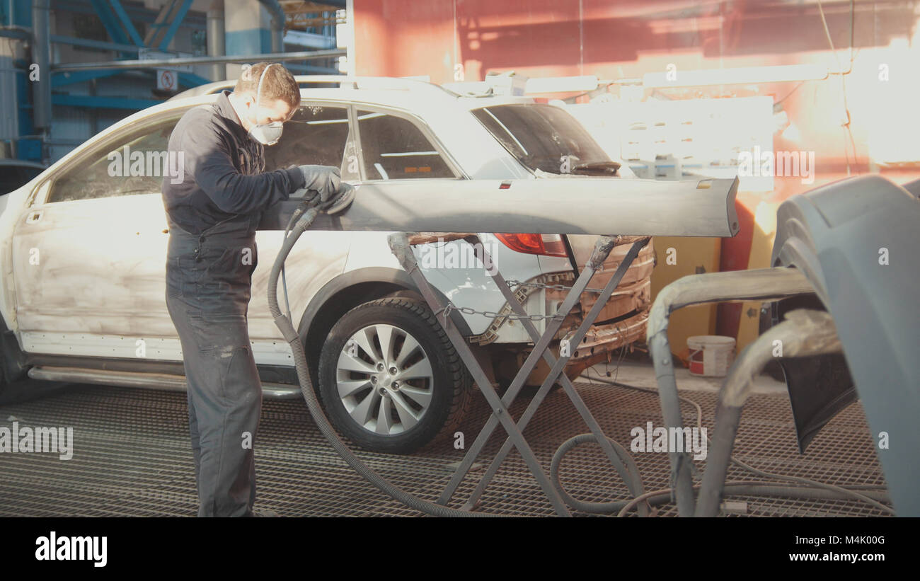 Process of repairing the vehicle - worker polishing detail of the car - Stock Image