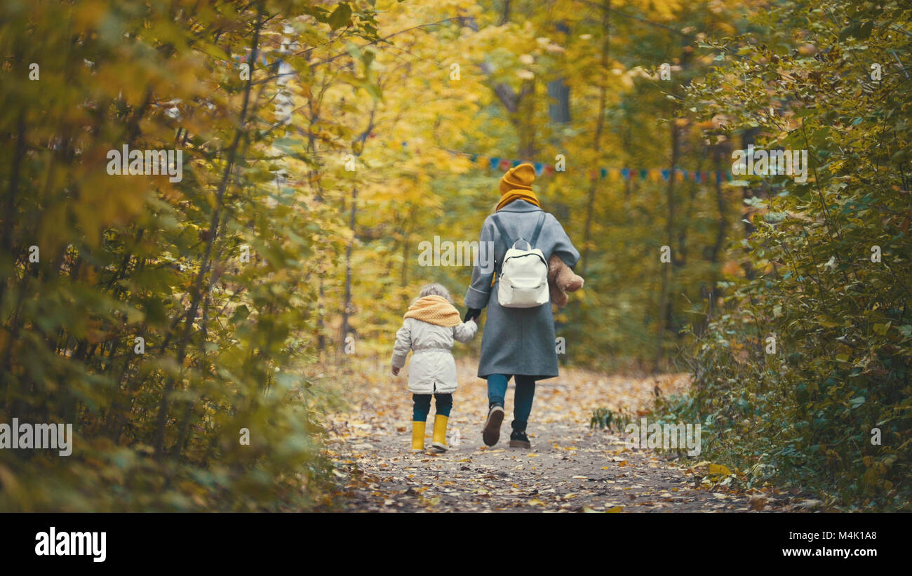 Joyful little daughter with her mommy and Teddy the Bear walks in autumn park, rear view - Stock Image