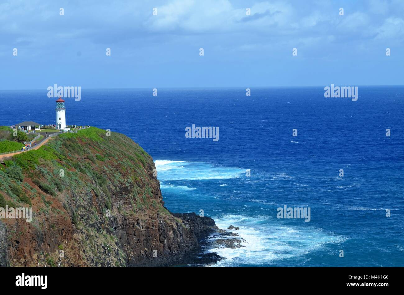 A lighthouse sits on top of a cliff, with the ocean below protecting and signaling the sailors of the danger, during - Stock Image