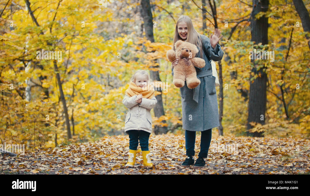 Pretty little daughter with her mommy plays with yellow leaves in autumn park - Stock Image