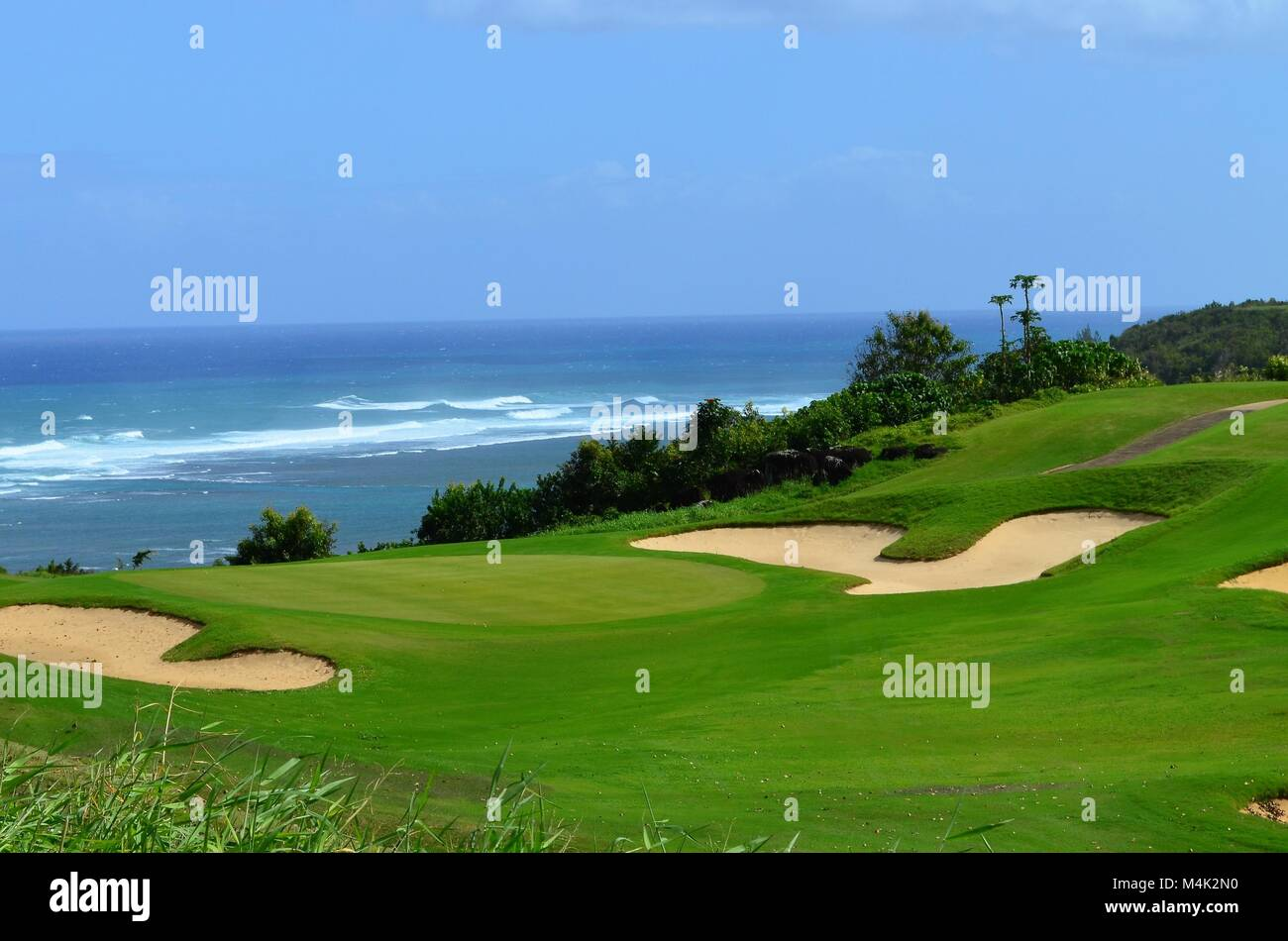 A scenic view of the white sand traps on a golf course over looking the ocean waves in the distance - Stock Image