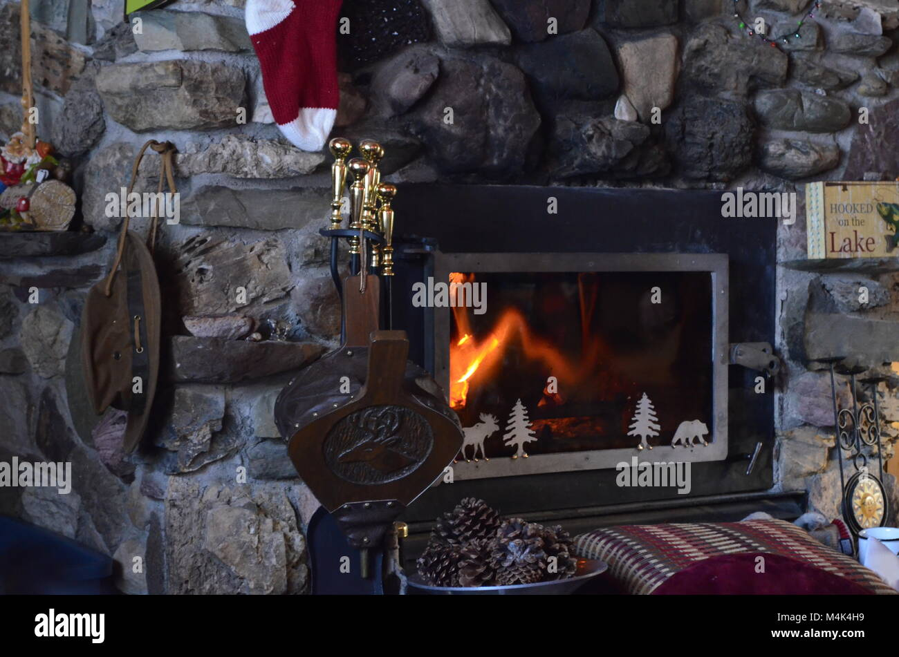 A floor to ceiling handmade stone fireplace, with a warm burning orange colored flame keeping the mountain cabin - Stock Image