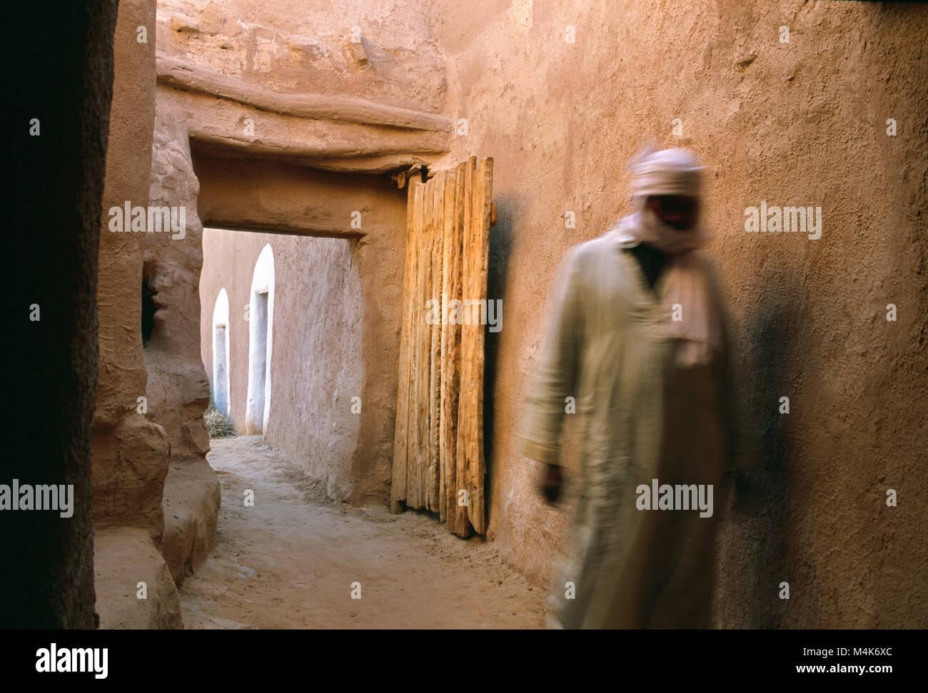 Algeria. Taghit or Tarit. Western Sand Sea. Grand Erg Occidental. Sahara desert. Oasis. Man walking in village. - Stock Image