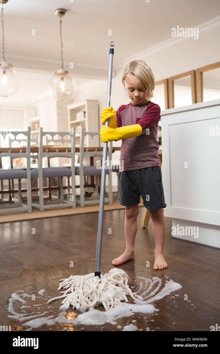 Boy washing the floor with mop - Stock Image