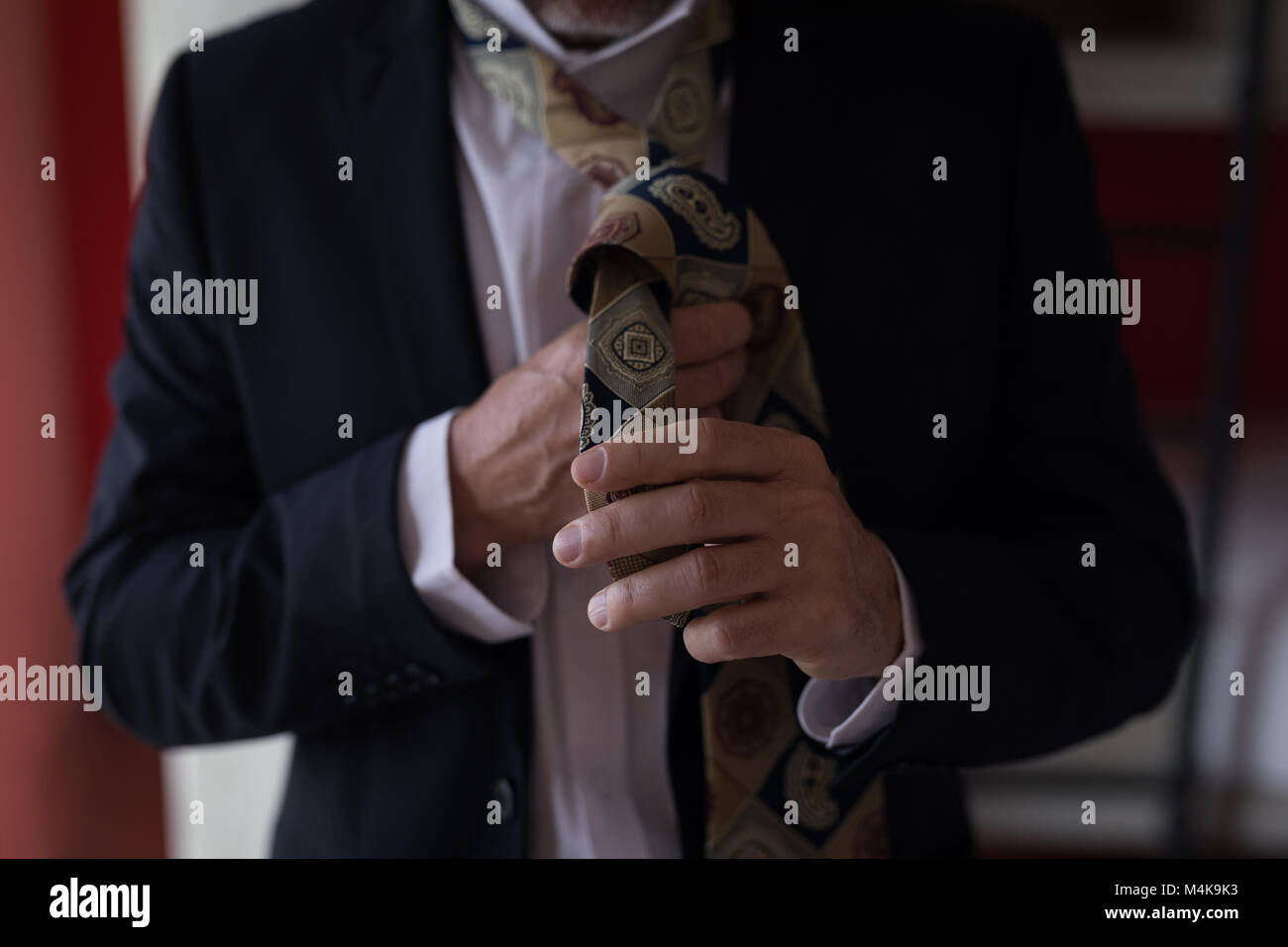 Businessman tying his tie - Stock Image