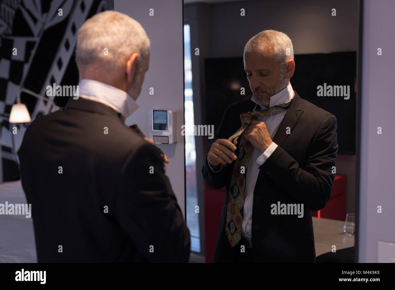 Businessman tying his tie in front of a mirror - Stock Image