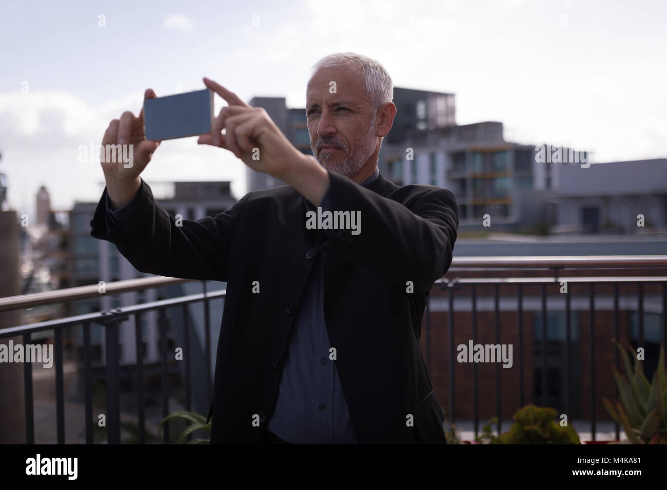 Businessman taking picture on mobile phone - Stock Image