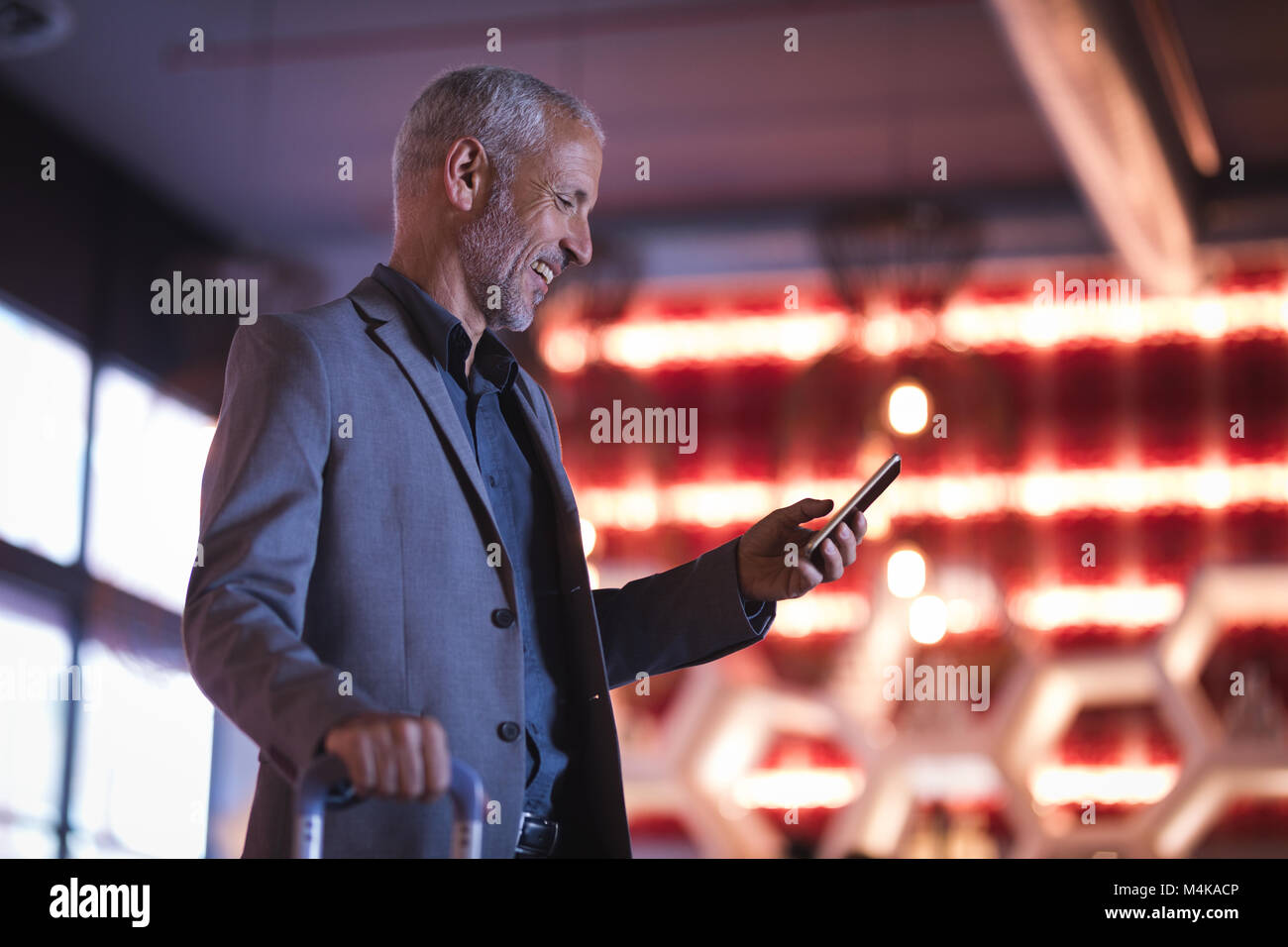 Businessman using smart phone while entering the hotel - Stock Image