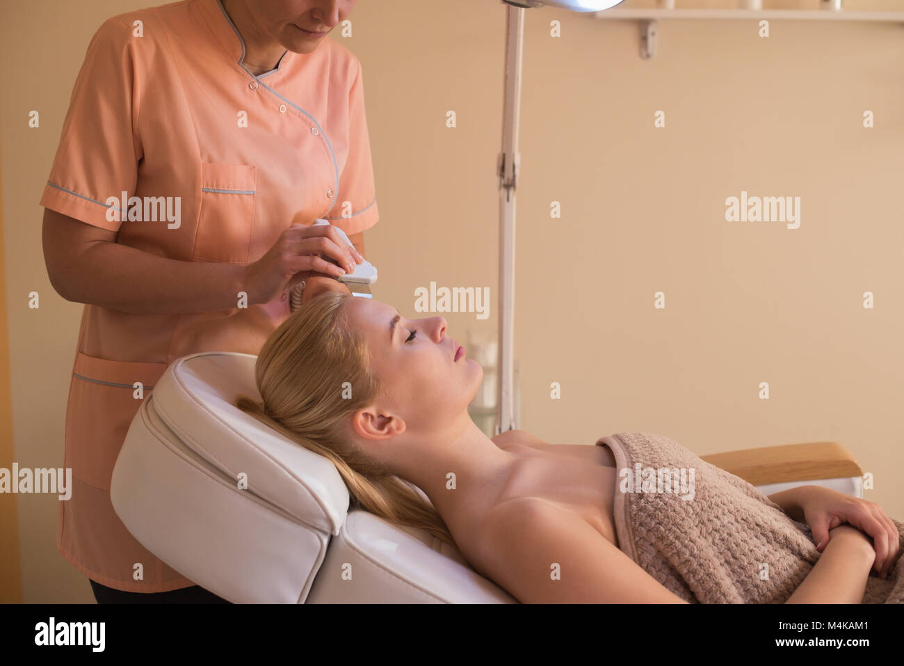Beautician using ultrasonic scrubber on female customer - Stock Image