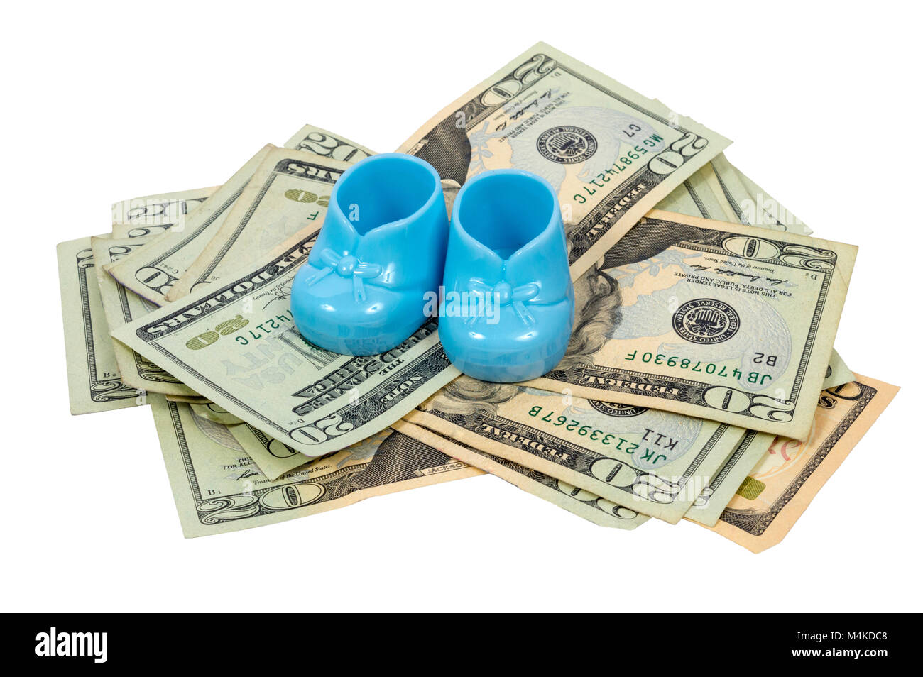 Horizontal shot of a pair of blue plastic baby booties resting on a pile of twenty dollary bills. - Stock Image