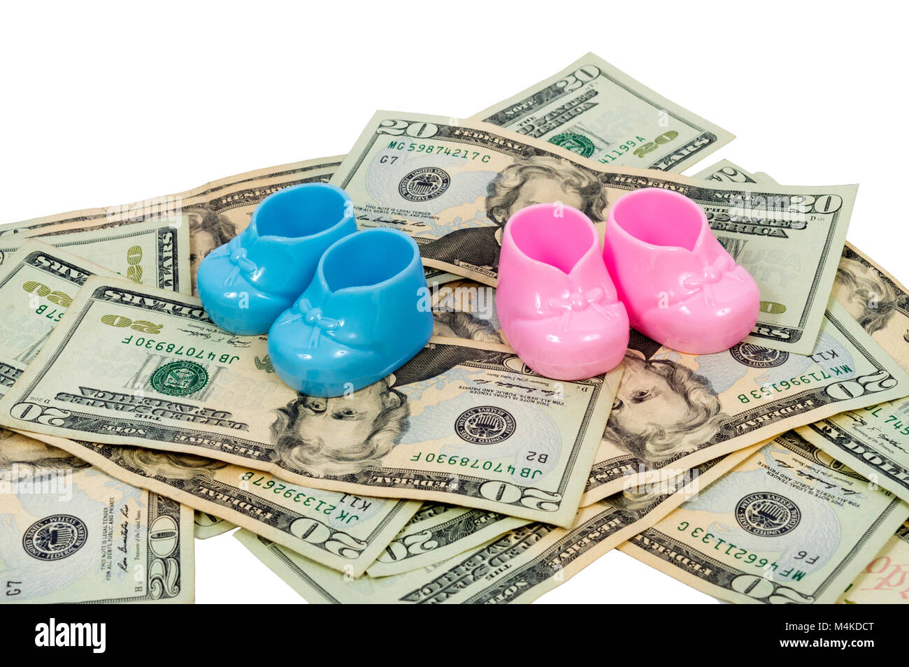 A horizontal shot of a pair of Blue and Pink Plastic Baby Booties Sitting on a Pile of Twenty Dollar Bills. - Stock Image