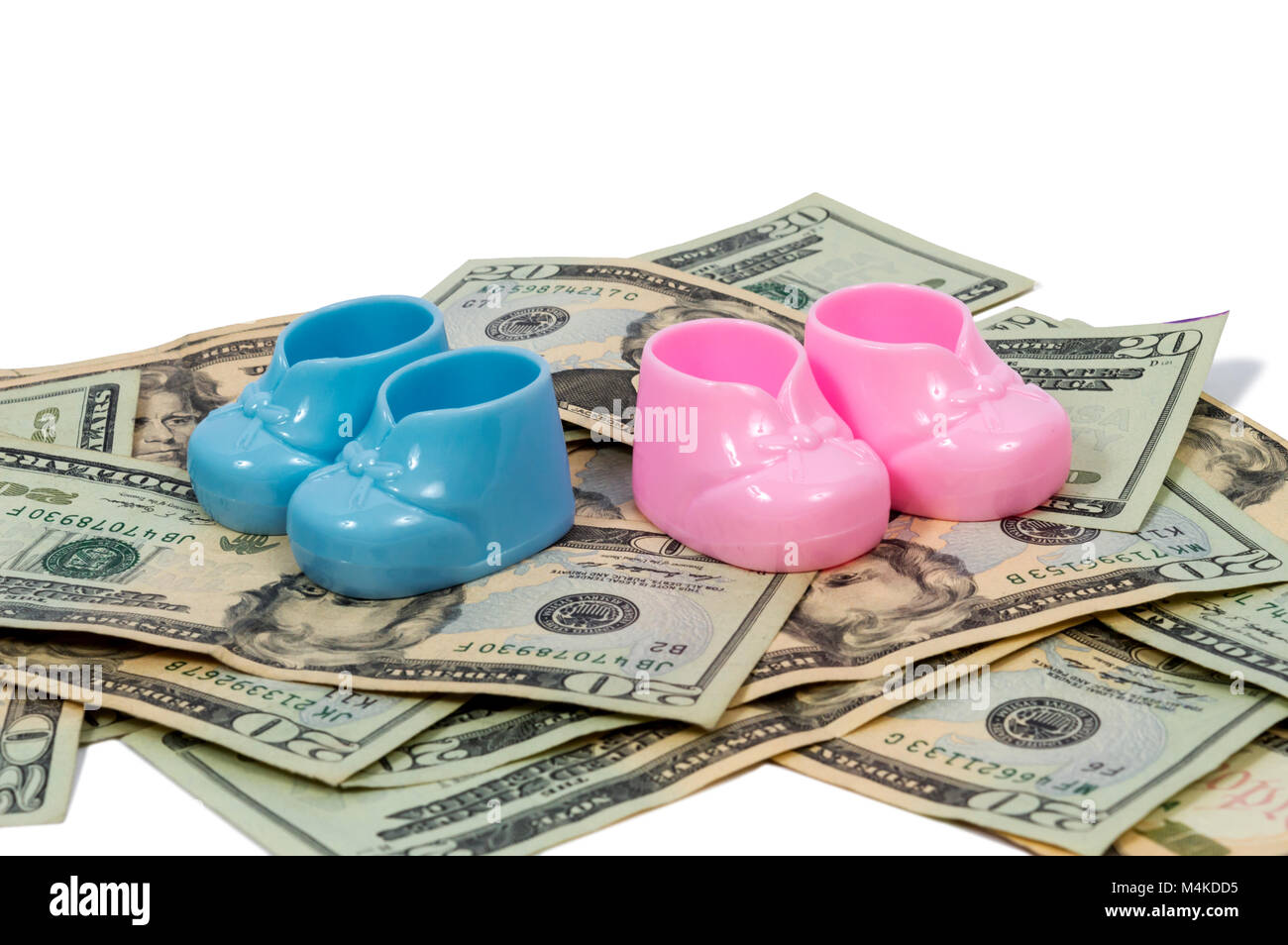 Horizontal shot of a pair of blue and pink plastic baby booties sitting on a pile of twenty dollar bills on a white - Stock Image