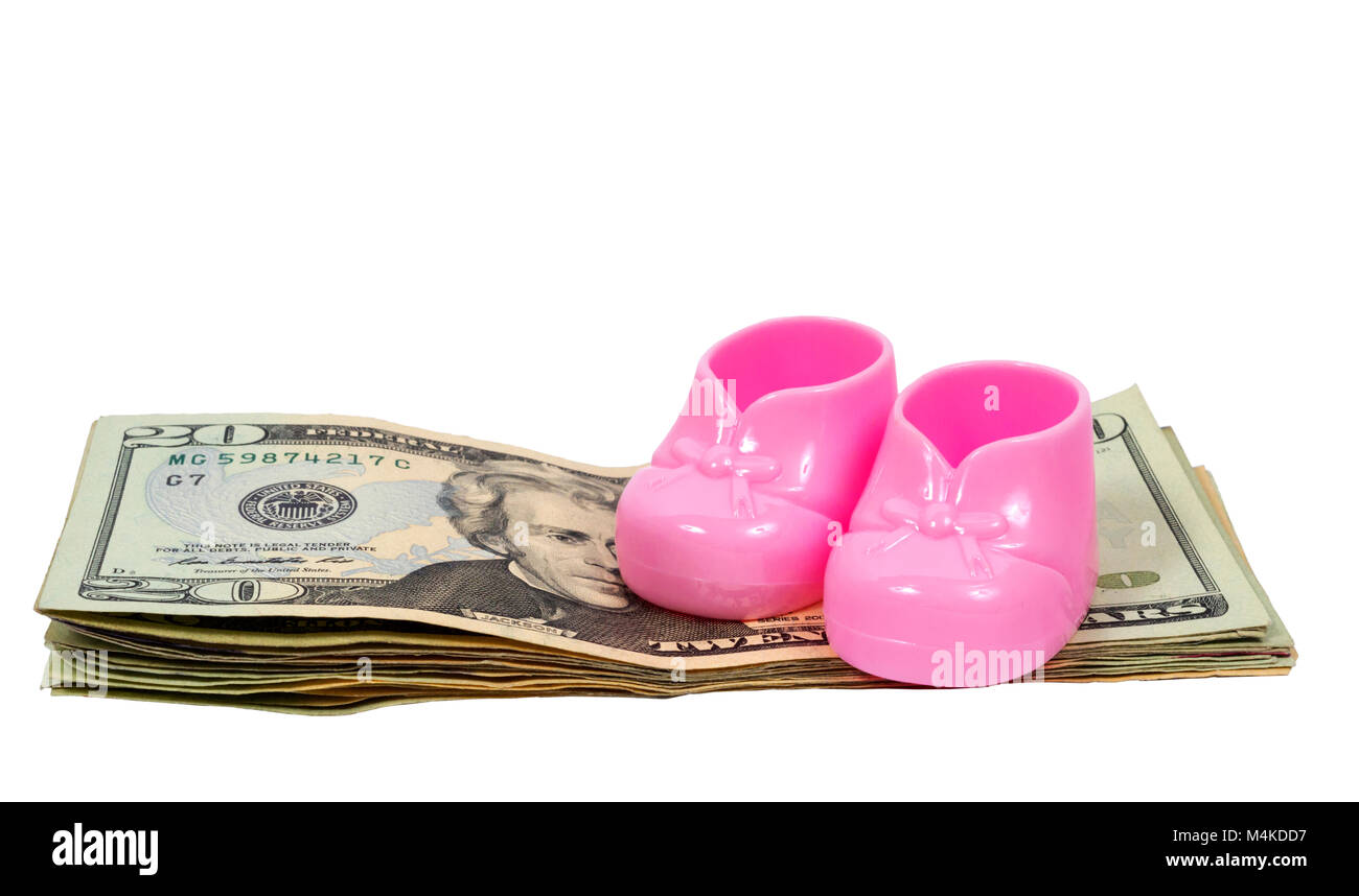 Horizontal shot of a pair of pink plastic baby booties sitting on top of a pile of twenty dollar bills on a white - Stock Image