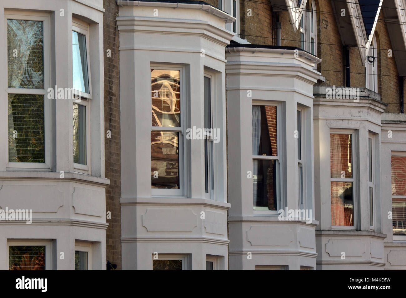 a row or line of terraced houses with bay windows on a street in a town centre. patterns formed by buildings in - Stock Image