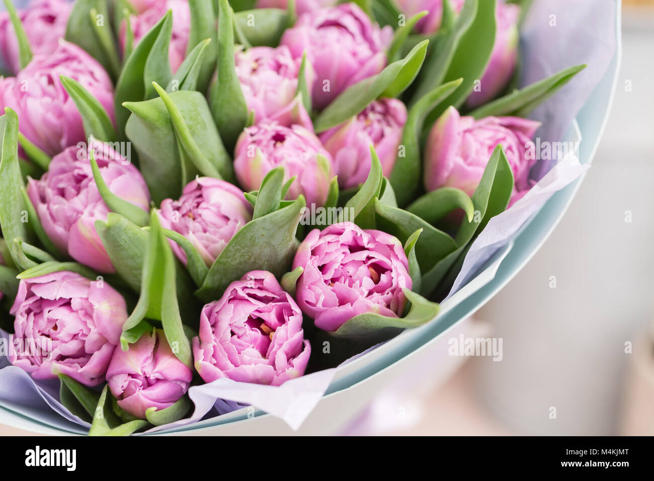 Close up beautiful luxury bouquet of lilac tulips flowers on table close up beautiful luxury bouquet of lilac tulips flowers on table the work of the florist at a flower shop izmirmasajfo