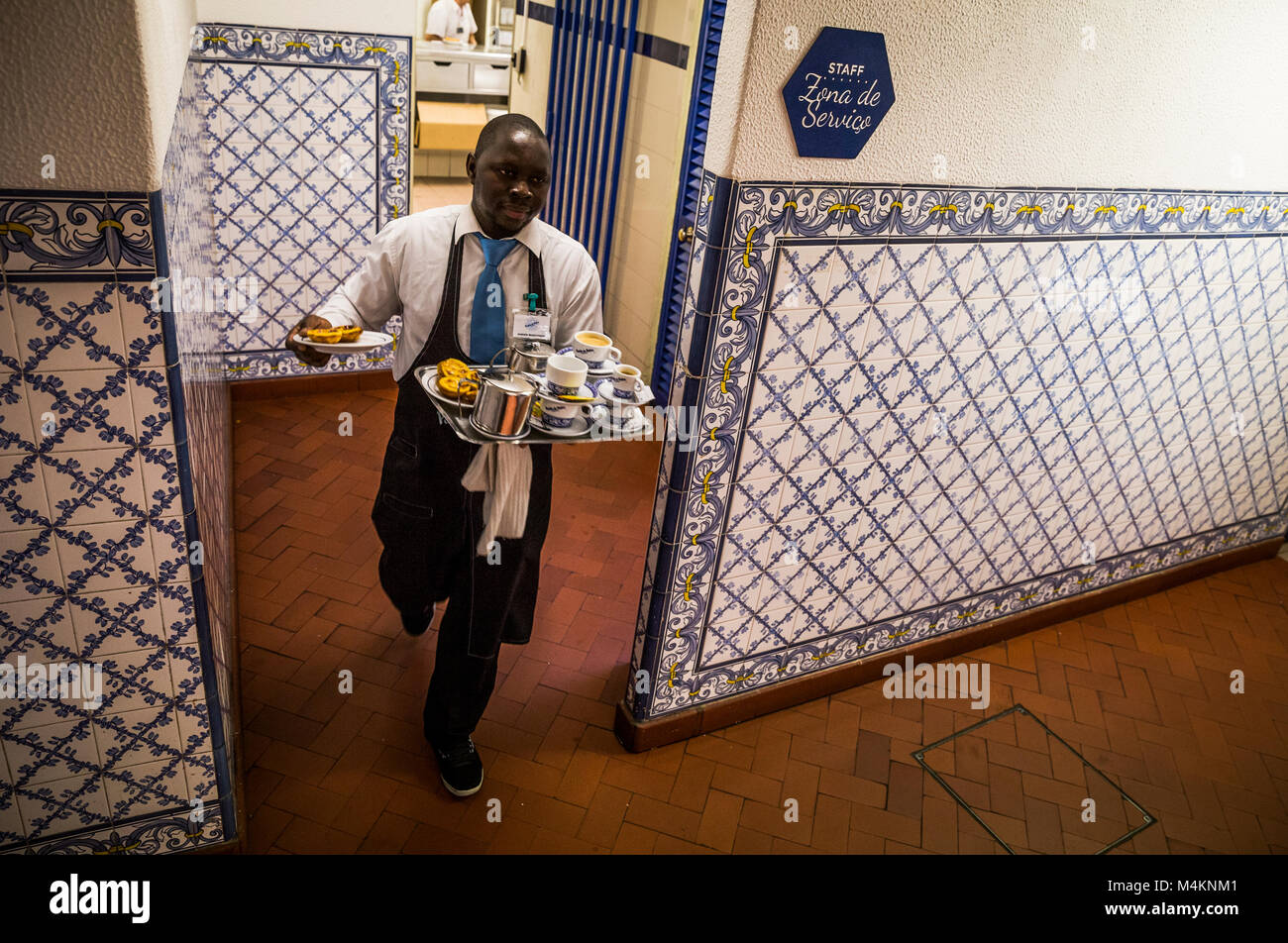 A waiter leaving the kitchen at Pasteis de Belem in Lisbon, Portugal. - Stock Image