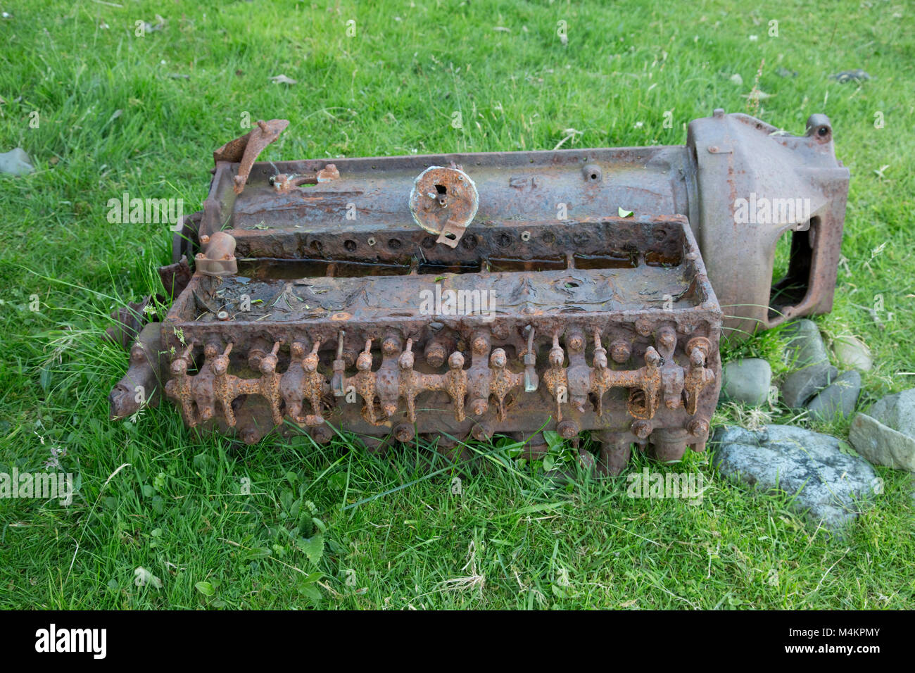 Old engine block rusting in field Scotland UK - Stock Image