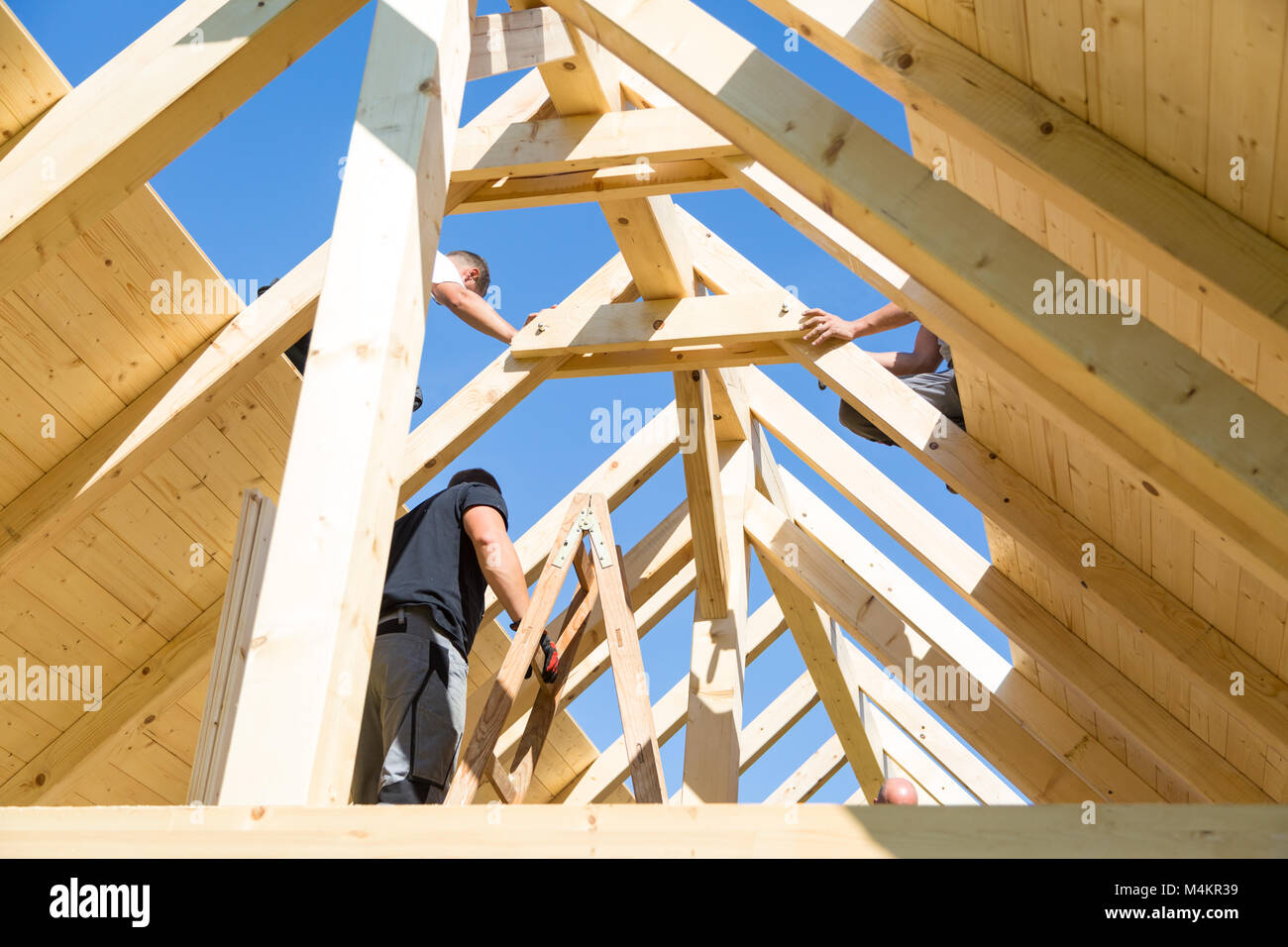 Builders At Work With Wooden Roof Construction Stock Photo